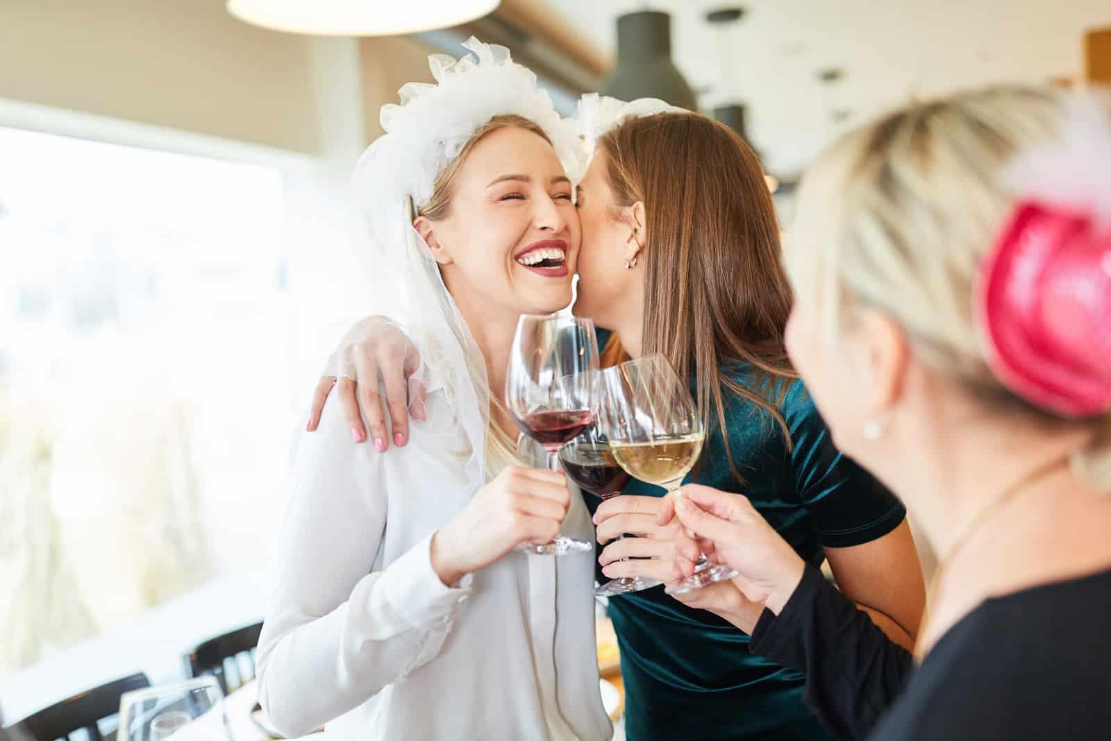 Lachende Braut mit Brautschleier wird von Freundin im Restaurant umarmt