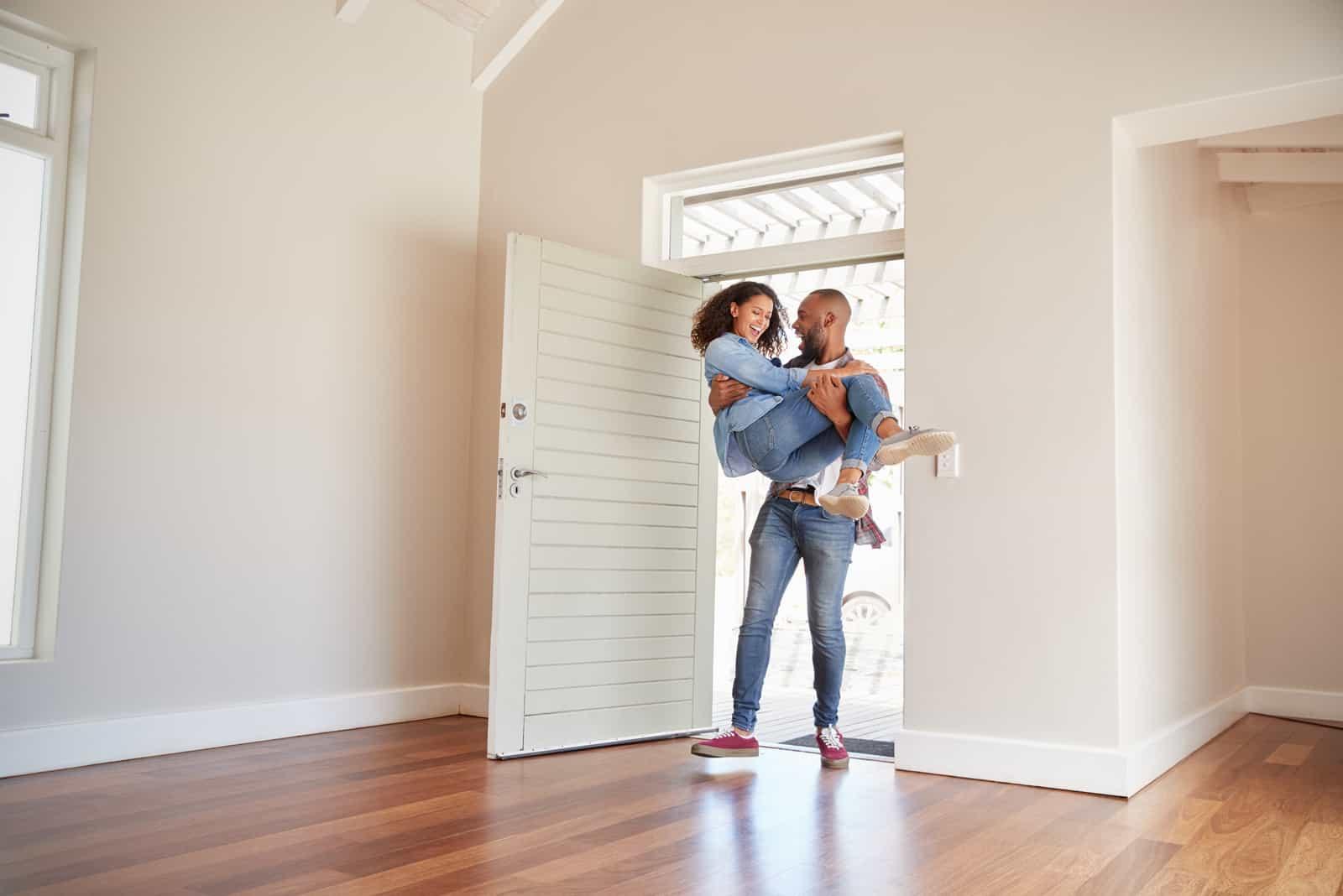 Mann, der Frau über Schwelle der Tür im neuen Haus trägt