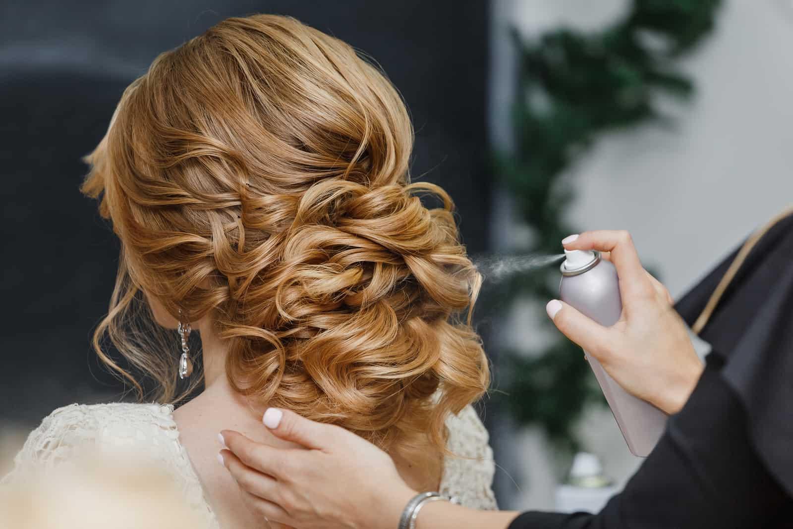 Master Stylist macht die Braut Hochzeit Frisur mit Sprühlack