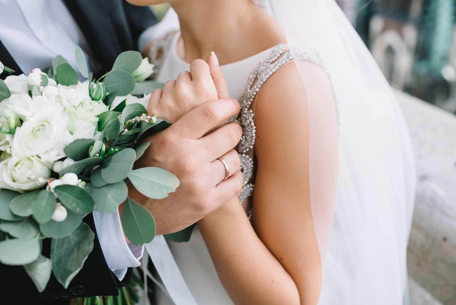 Nahaufnahme der Hand des Bräutigams, die den Willen der Braut hält