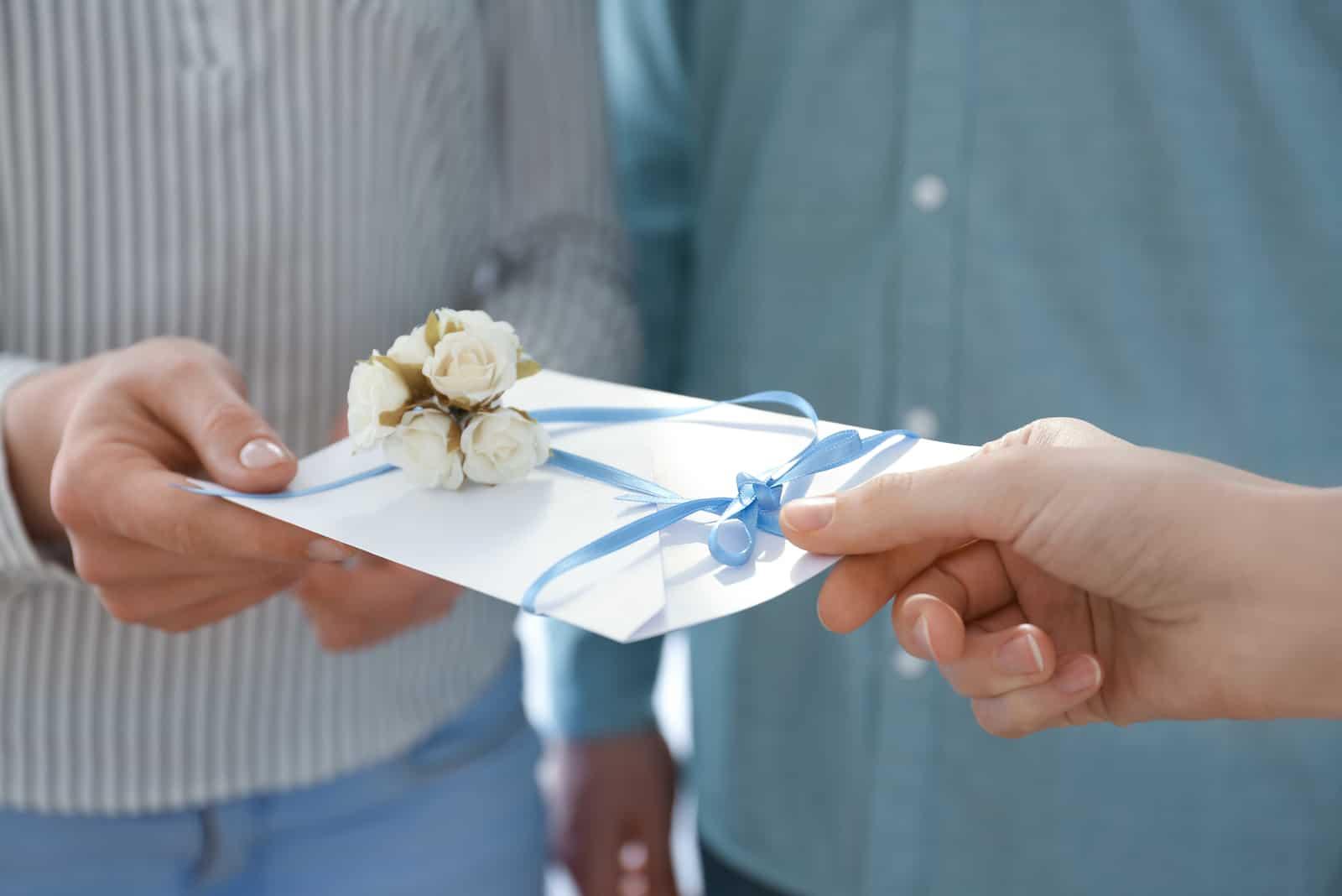 Paar, das Hochzeitseinladung, Nahaufnahme empfängt