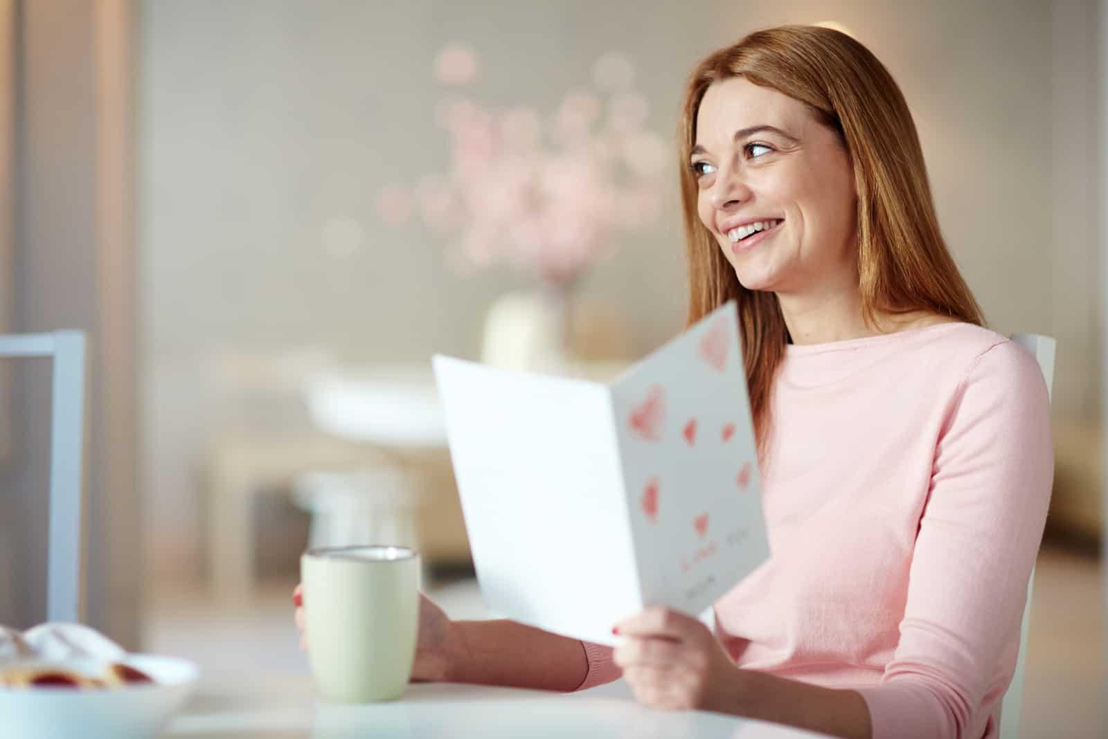 Ruhige junge Frau mit der Tasse, die Einladungskarte liest