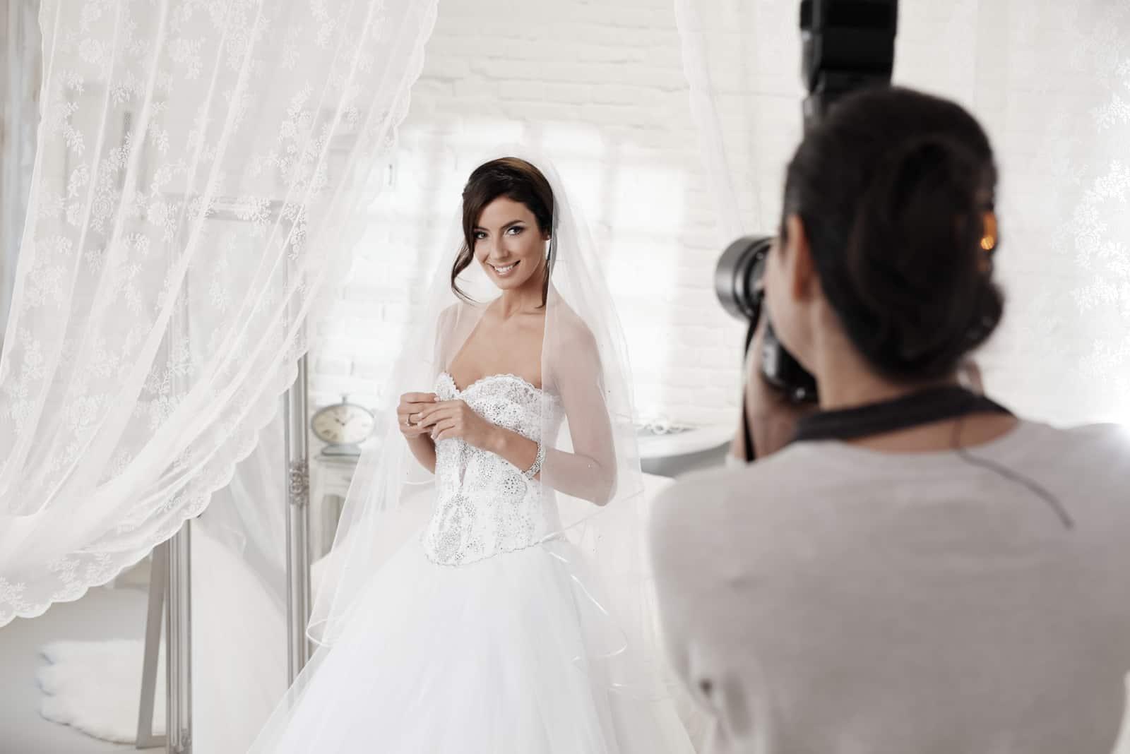 Schöne Braut, die Front des Fotografen im weißen Innenraum aufwirft