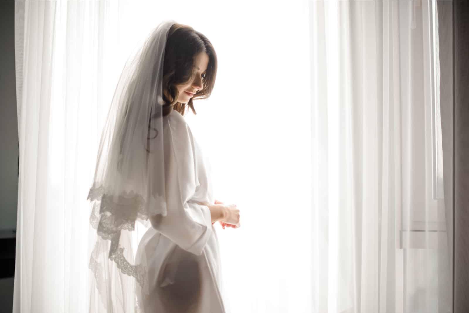 Schöne Braut im weißen Hochzeitskleid und im Schleier
