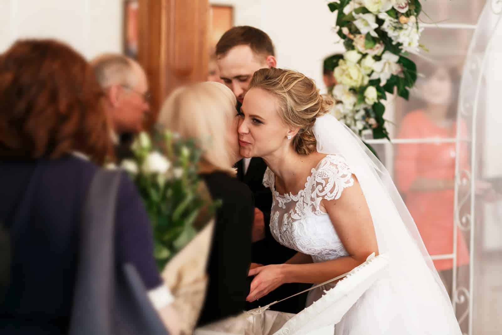 Schöne stilvolle Braut und Bräutigam unter den Hochzeitsgrüßen von den Gästen