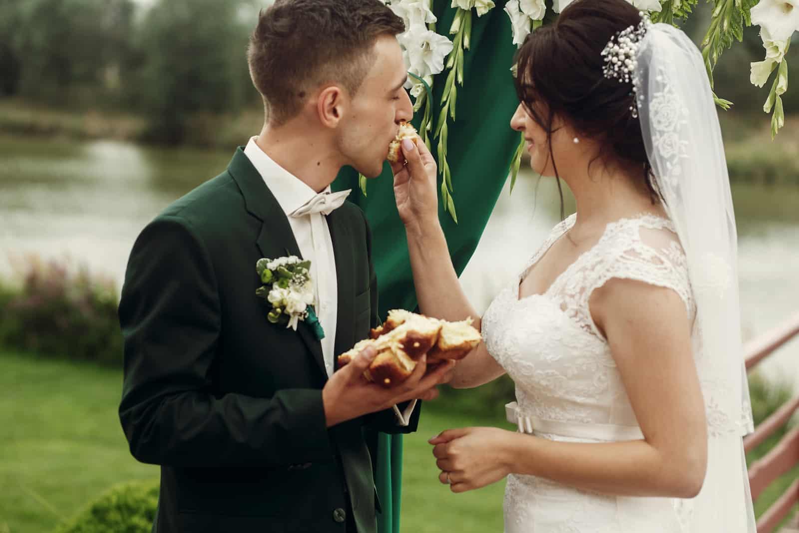 frisch verheiratetes Paar, das Brot bei der Hochzeitszeremonie bricht