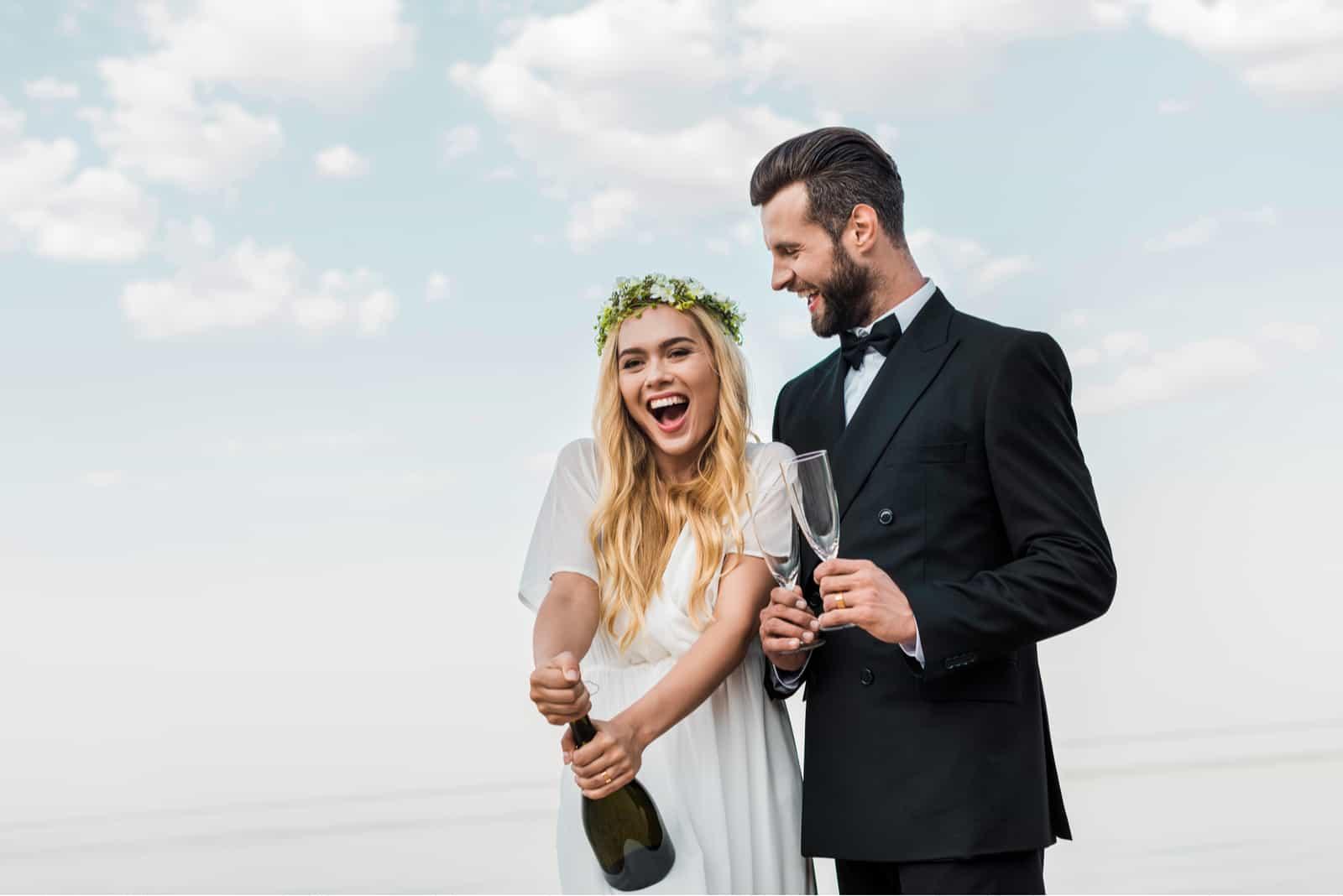 glückliche Braut im weißen Kleid, das Champagnerflasche am Strand öffnet