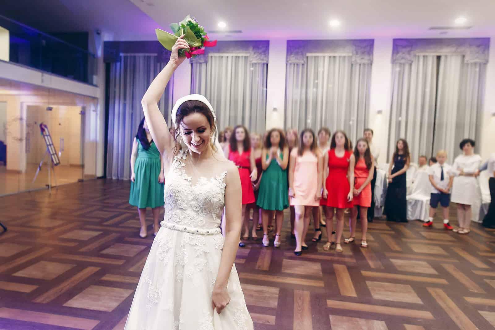 lächelnde Braut im Weinleseweißhochzeitskleid, das Brautjungfernstrauß wirft