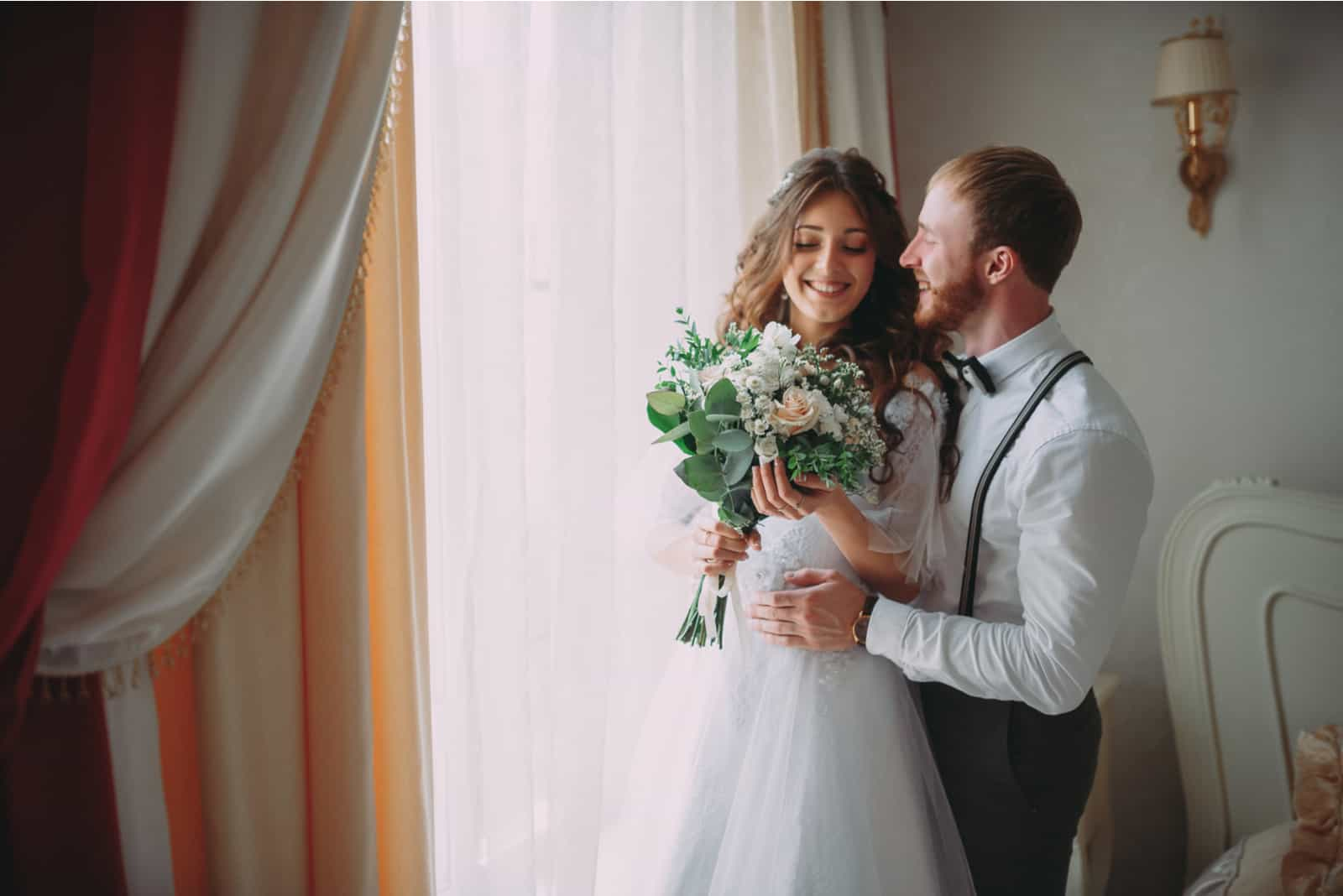 stilvoller Bräutigam mit Bart und schöner Braut, die im Hotel aufwirft