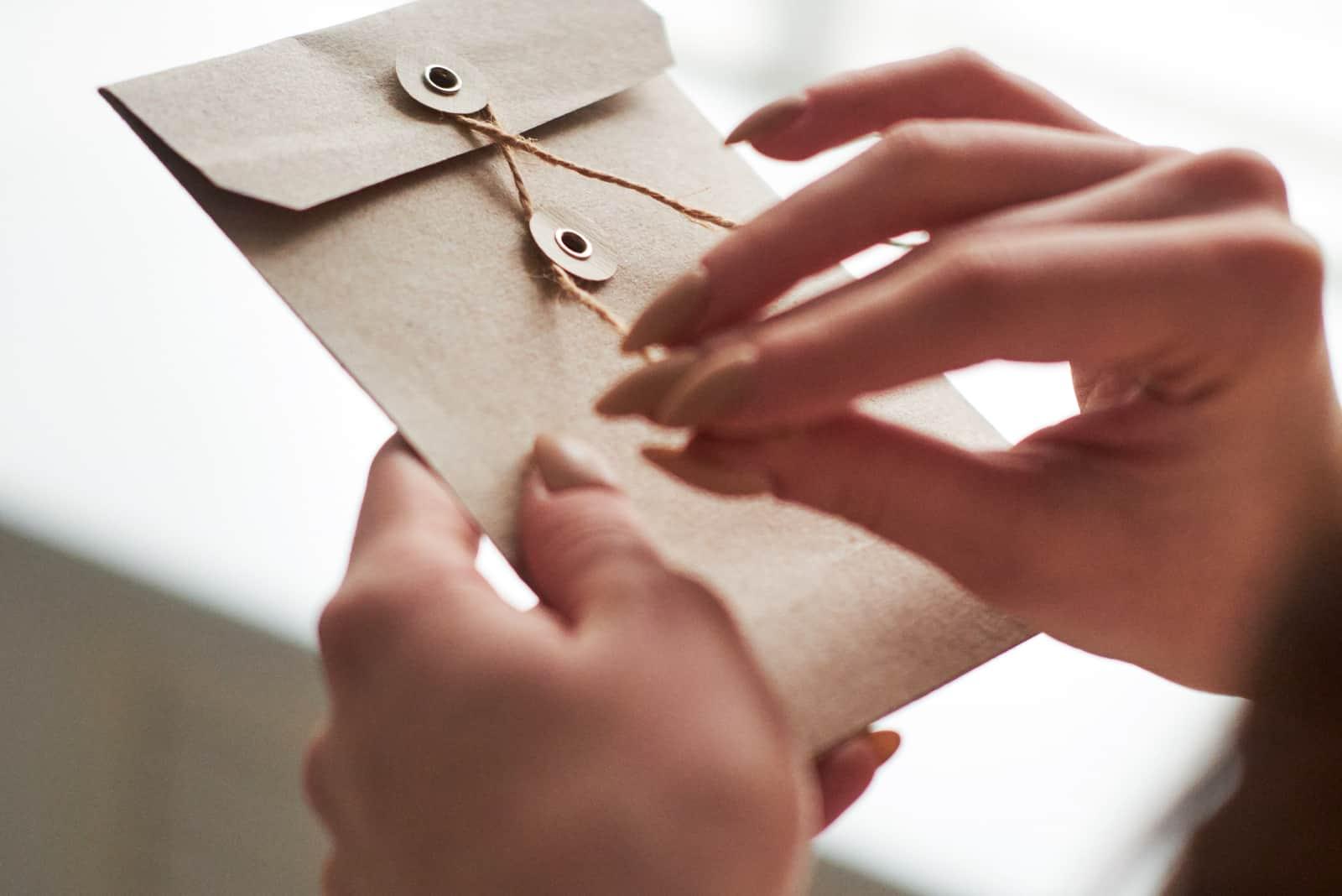 weibliche Frauenhand, die einen Umschlag hält und öffnet