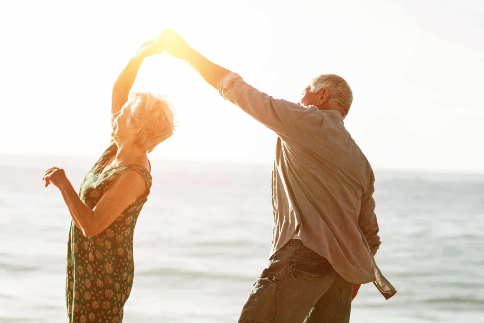 Älteres Paar, das am sonnigen Tag am Strand tanzt