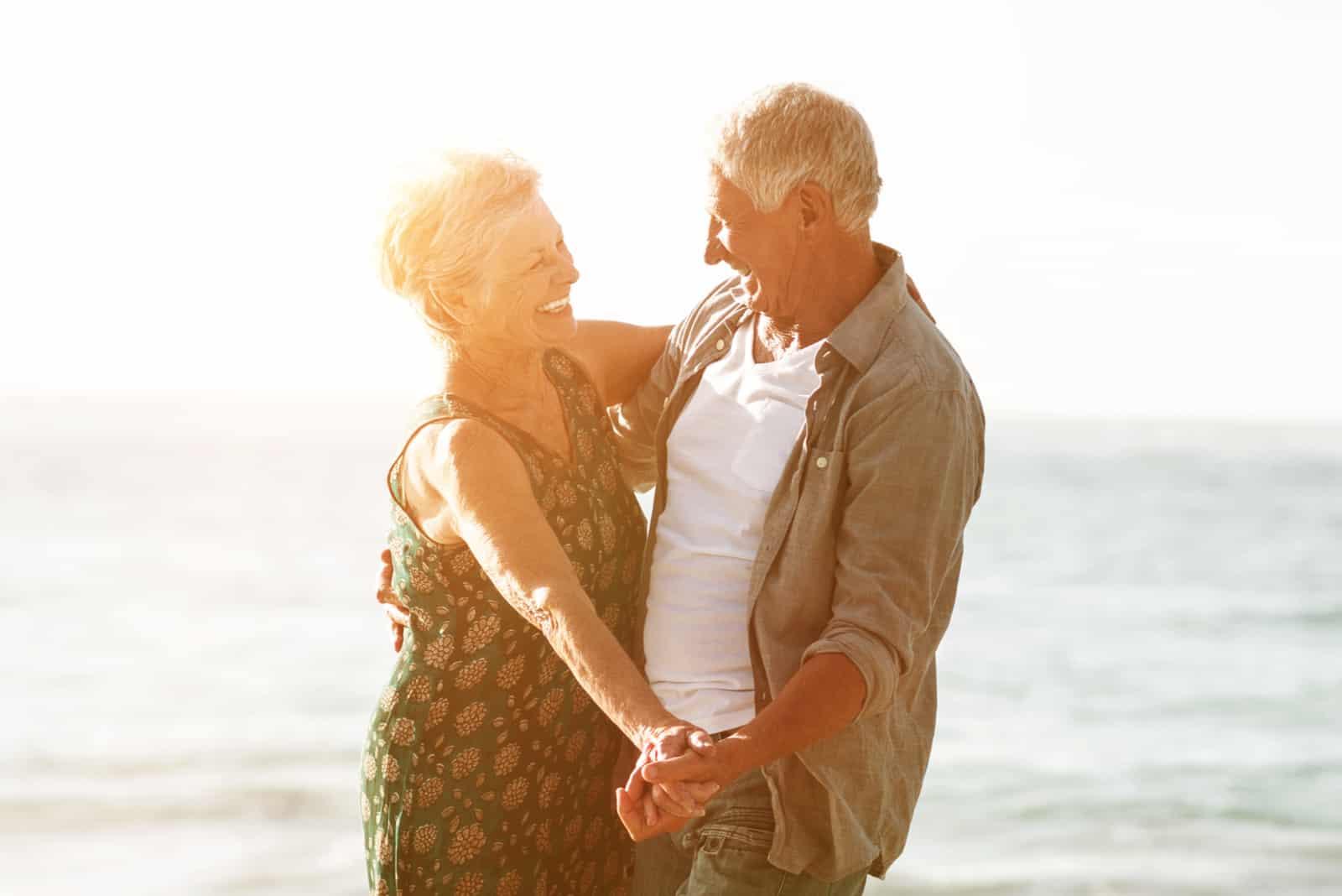 Älteres Paar, das an einem sonnigen Tag am Strand tanzt