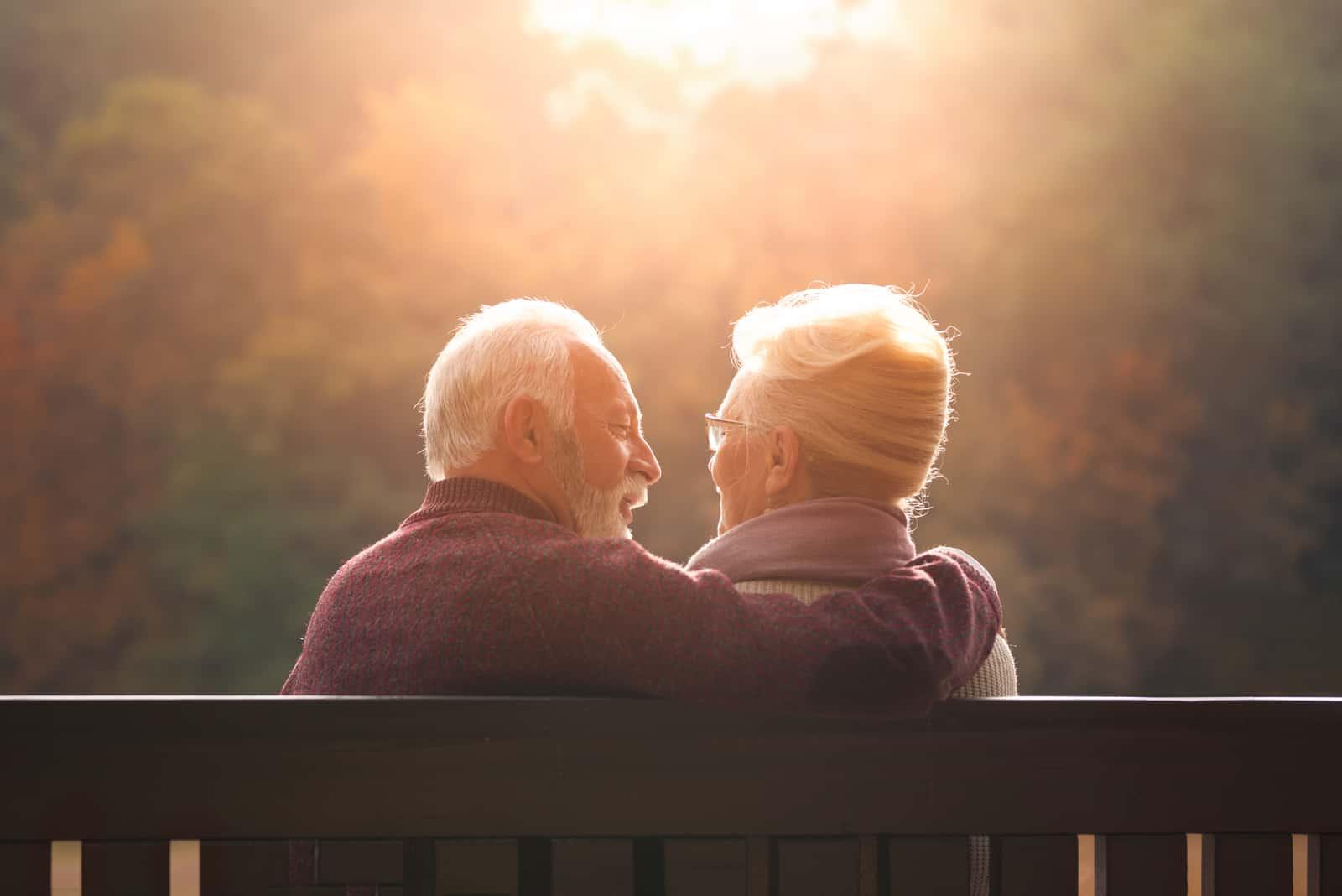 Älteres Paar, das auf Bank im Herbstpark sitzt und Sonnenuntergang schaut