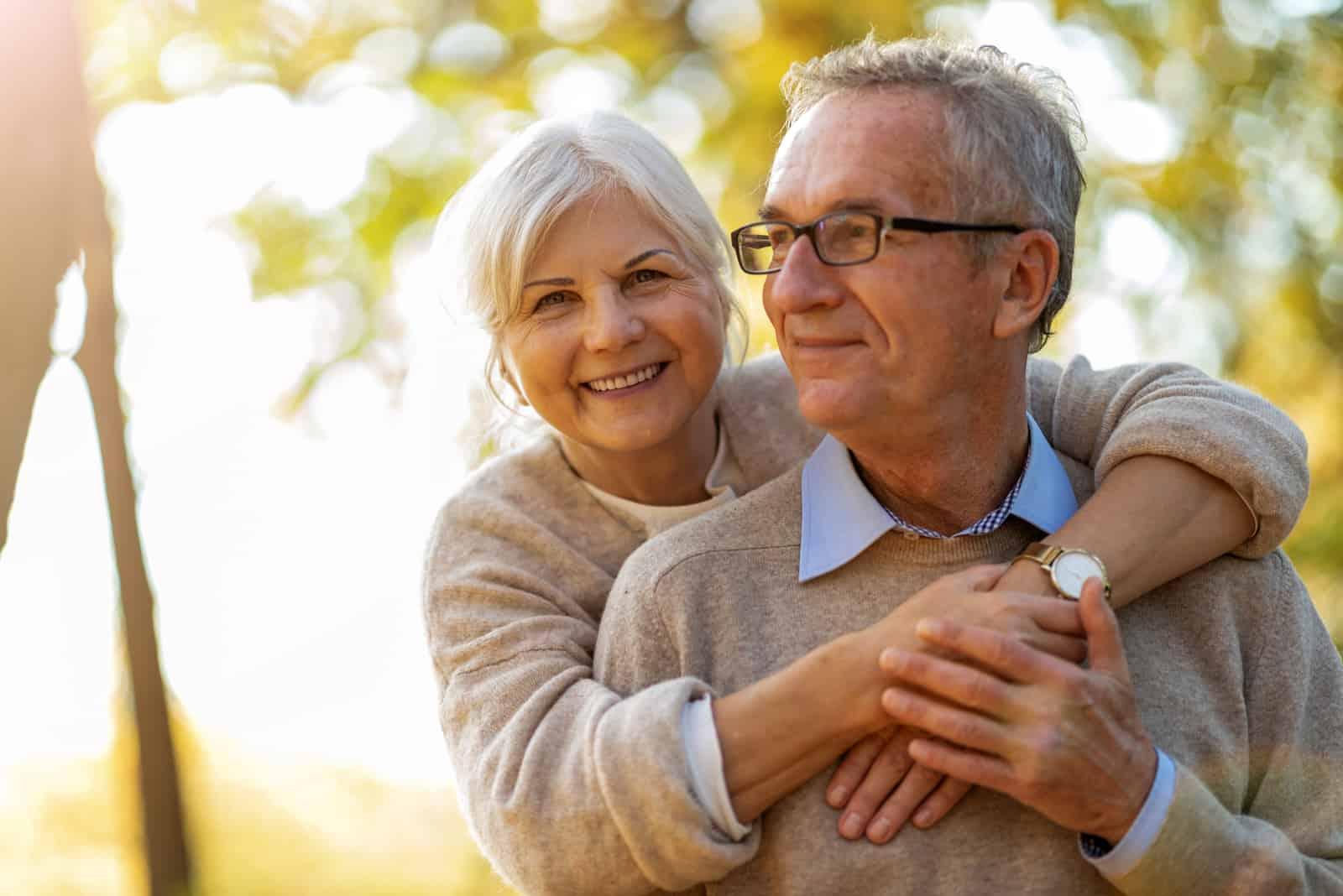 Älteres Paar, das im Herbstpark umarmt