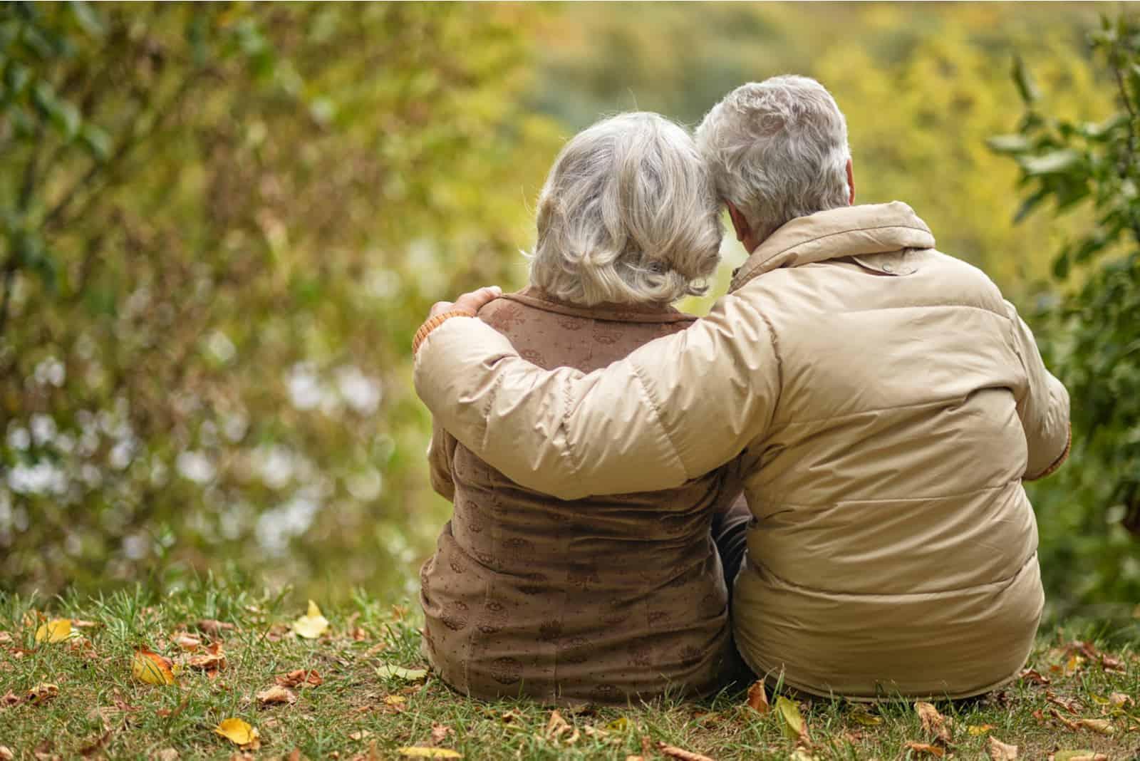 Älteres Paar, das mit dem Rücken sitzt, der im Herbstpark umarmt