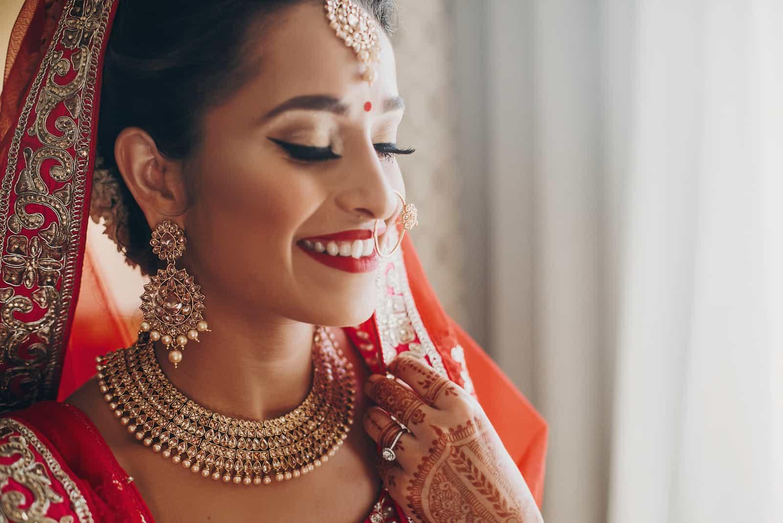 Atemberaubende indische Braut gekleidet in hinduistischen roten traditionellen Hochzeitskleidern