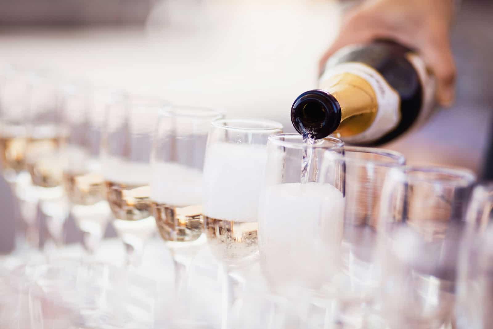 Barkeeper gießt Champagner in Gläser (1)
