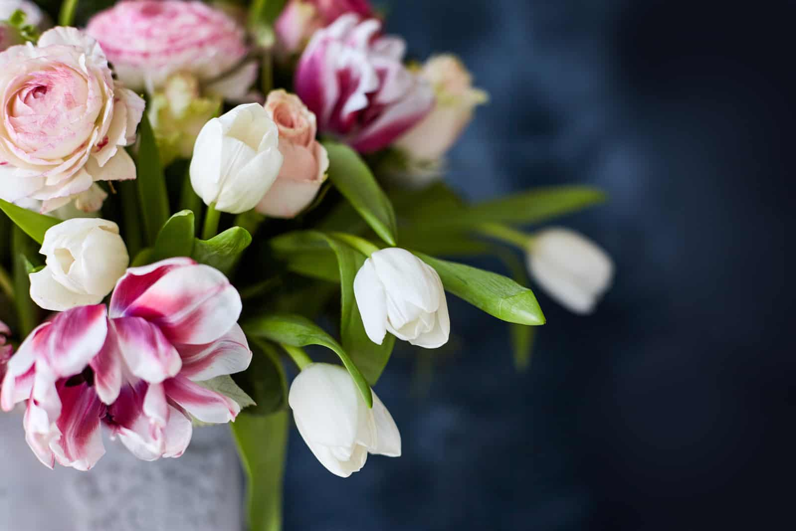 Blumenarrangement mit Tulpen und Ranunkeln auf weißem Holzboden