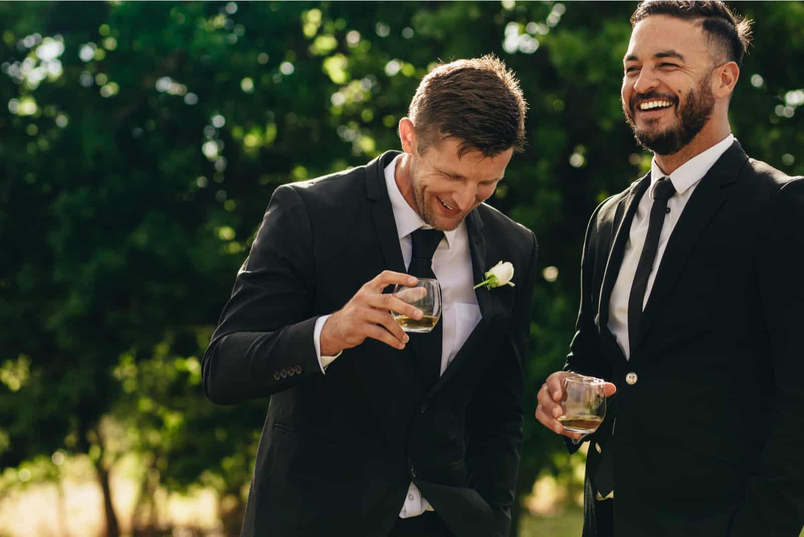Bräutigam und Trauzeuge trinken und lächeln während der Hochzeitsfeier (1)