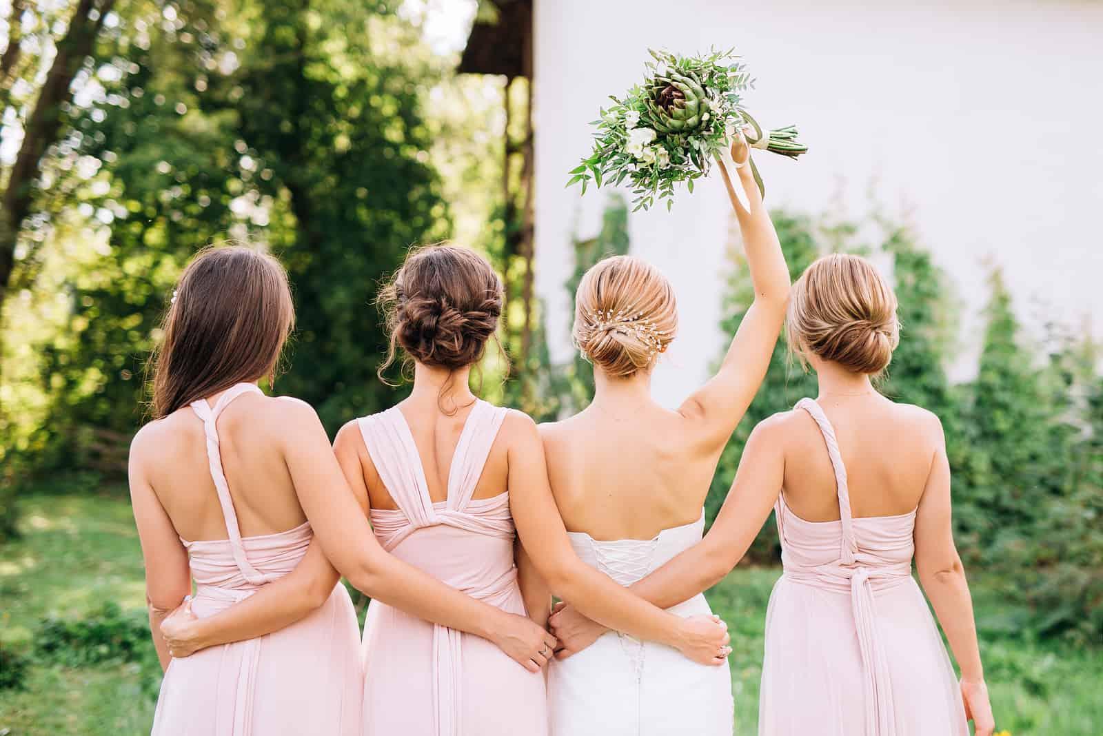 Braut, die mit ihrem Rücken in einem weißen Hochzeitskleid steht