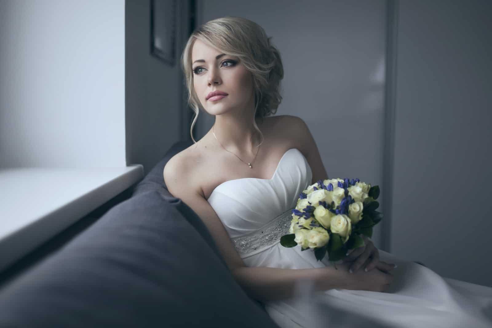 Braut im weißen Hochzeitskleid mit Brautstrauß