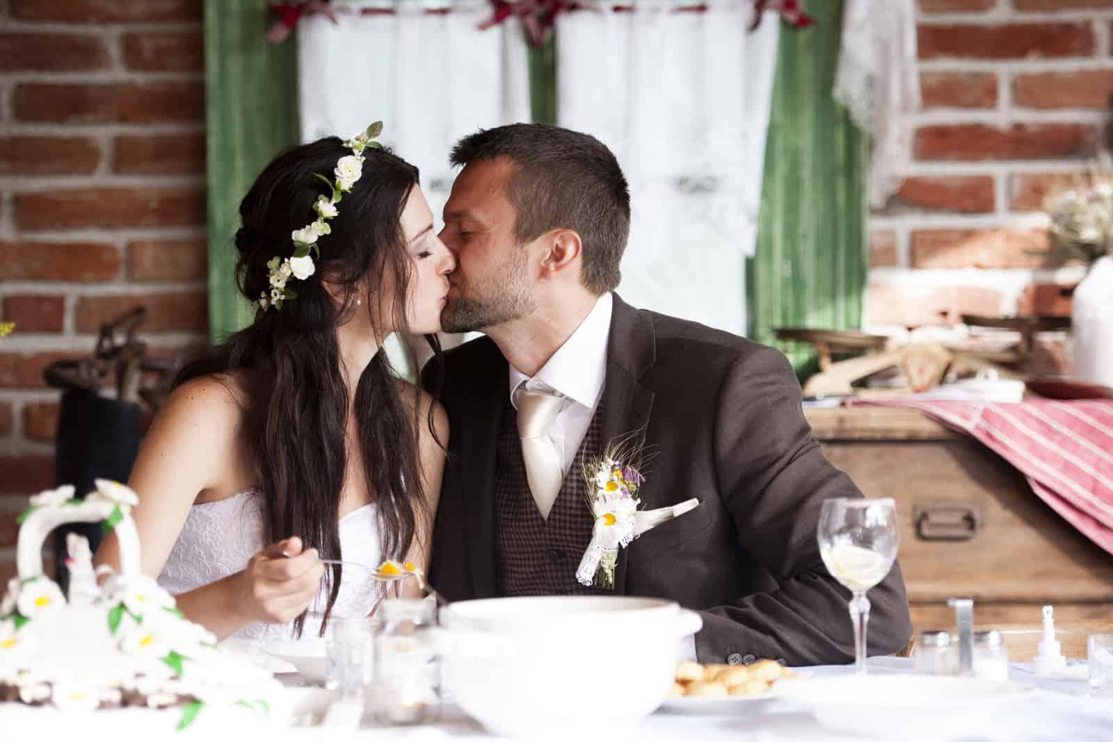Braut und Bräutigam essen auf der Hochzeitsfeier