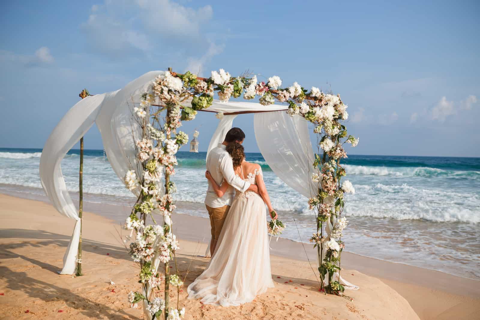 Braut und Bräutigam genießen Strandhochzeit