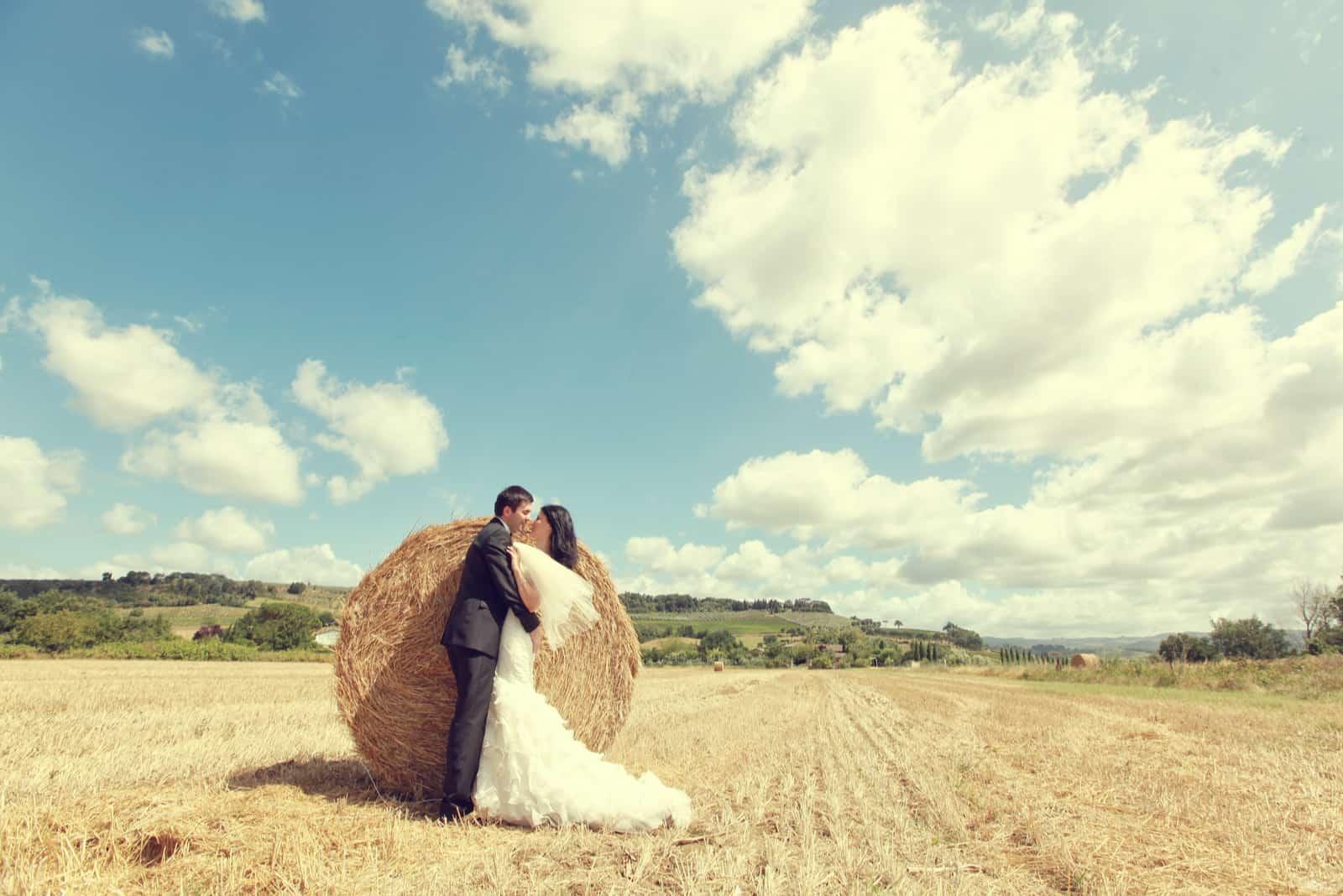 Braut und Bräutigam küssen in einem Weizenfeld