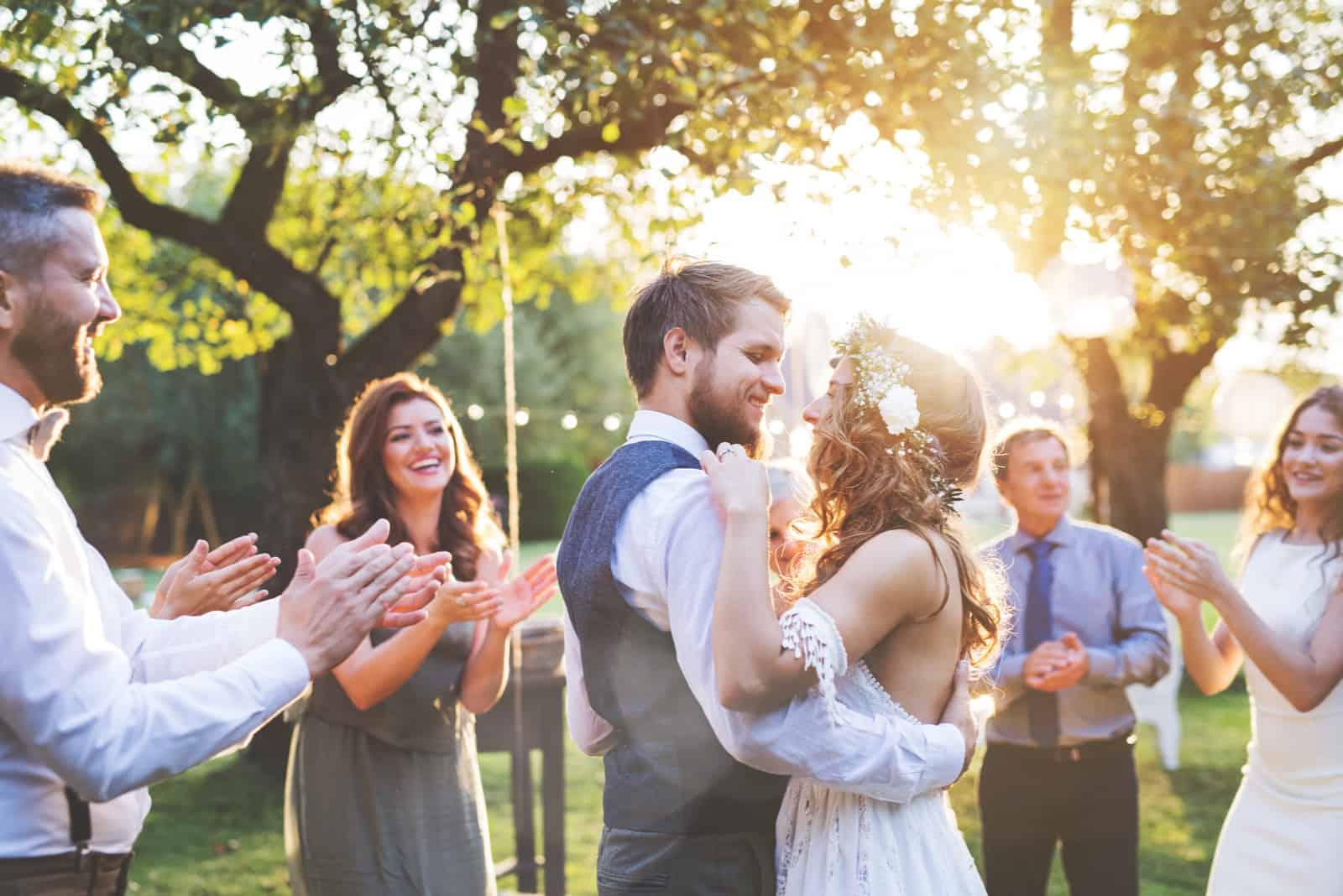 Braut und Bräutigam tanzen auf Hochzeitsempfang draußen