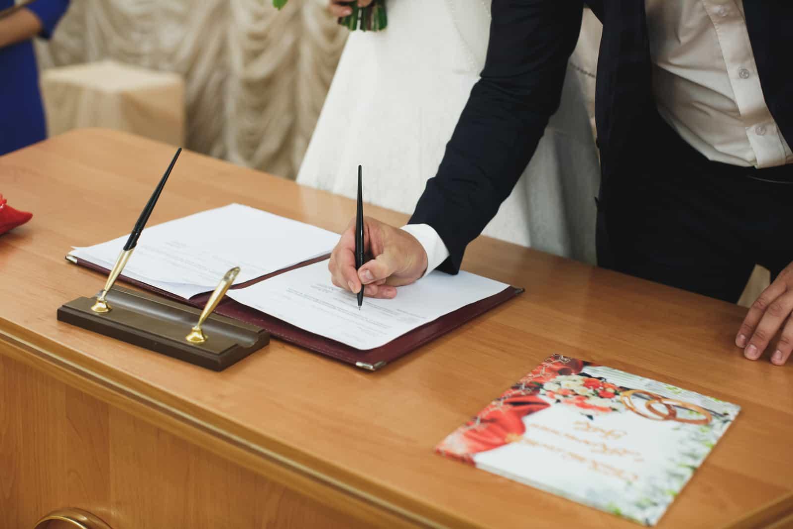 Braut und Bräutigam unterzeichnen Hochzeit Hochzeitsurkunde bei der Registrierung