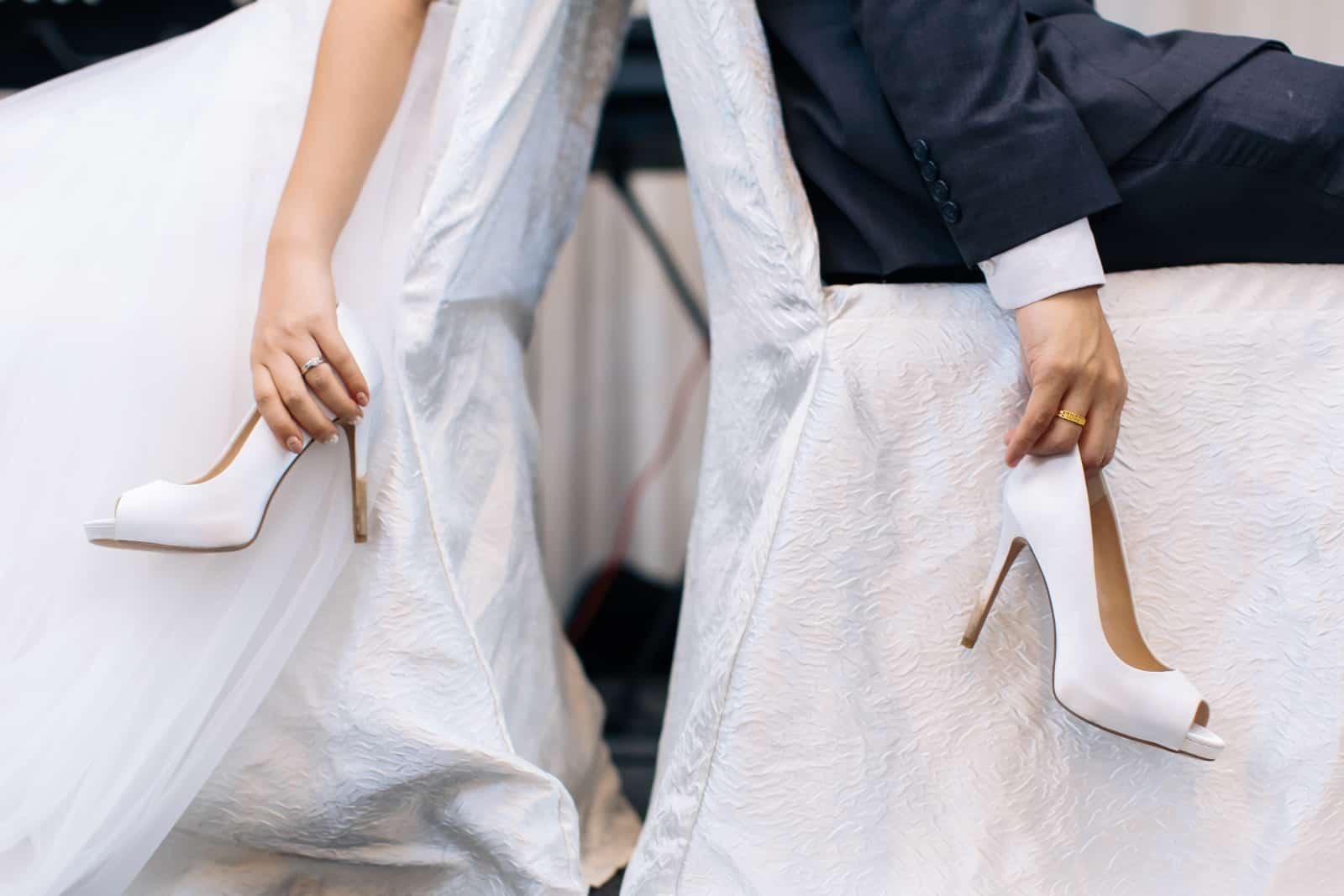 Braut und Bräutigam halten jeweils einen Schuh von der Braut fern