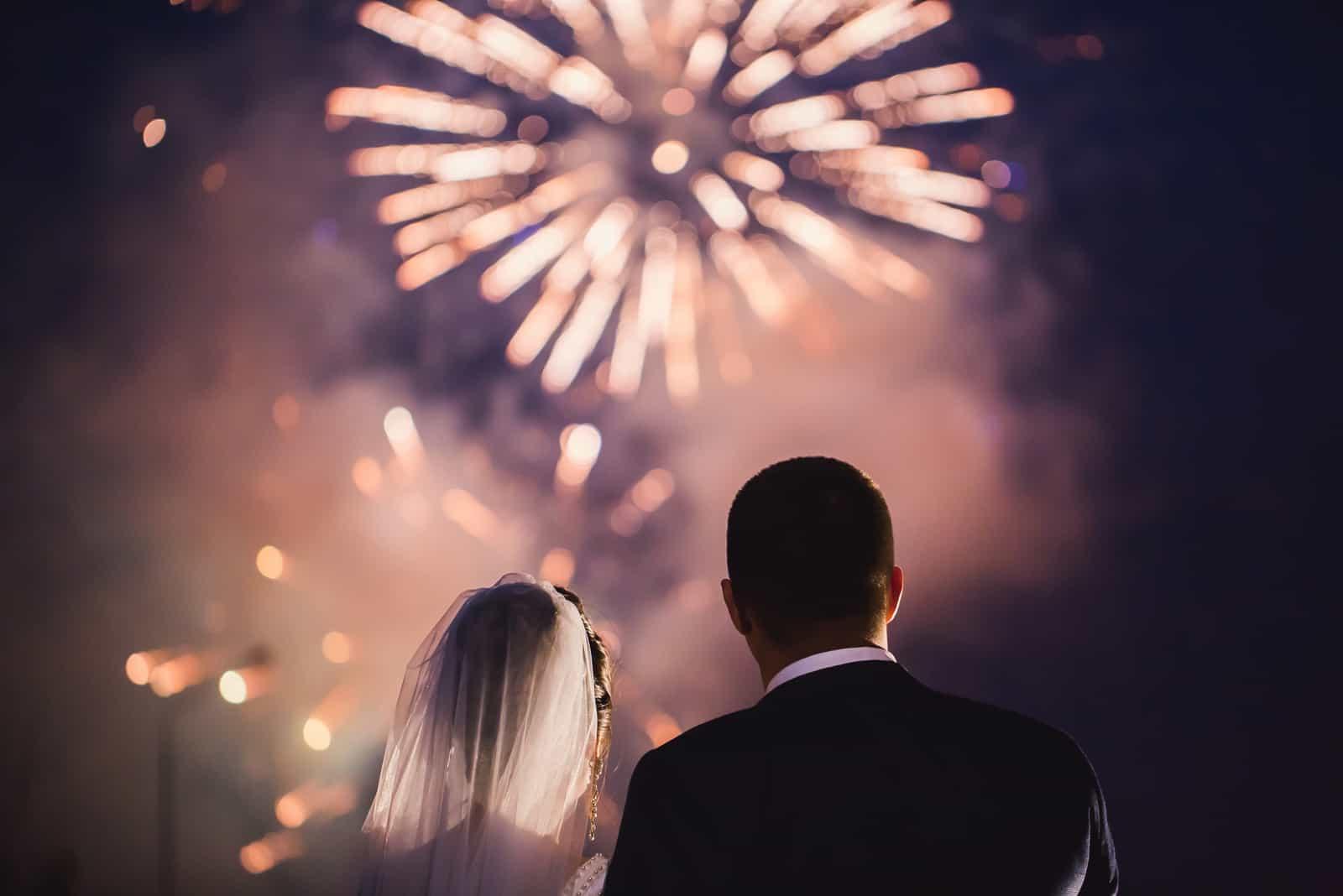 Braut und Bräutigam schauen sich das Feuerwerk an