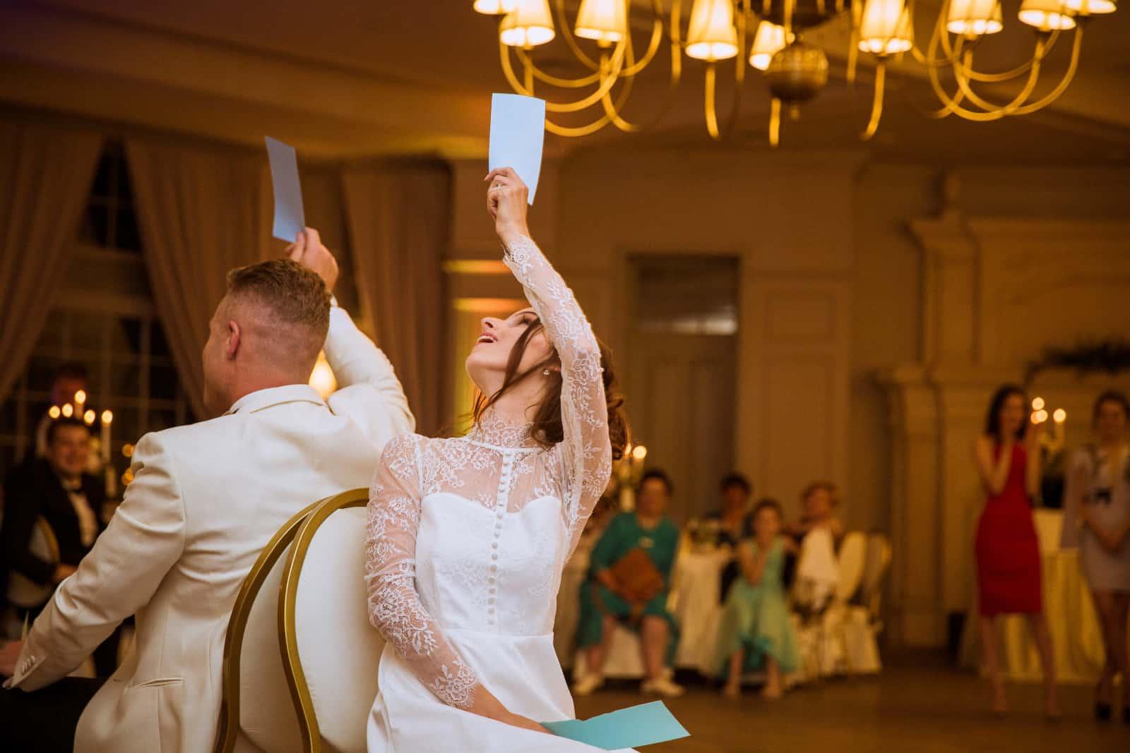 Braut und Bräutigam sitzen auf Stühlen mit Papieren in der Luft