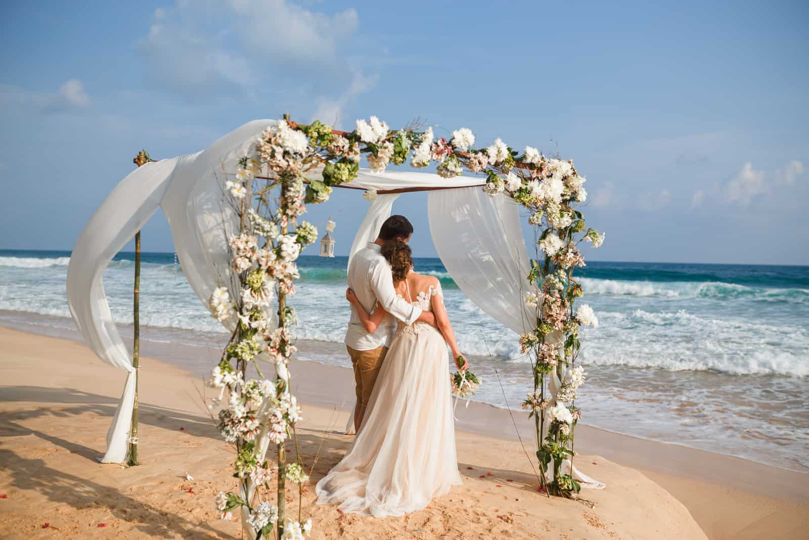 Braut und Bräutigam umarmen sich am Strand