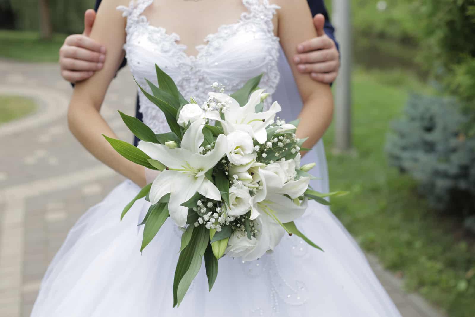 Braut und Bräutigam werden im Park mit einem Strauß weißer Lilien fotografiert