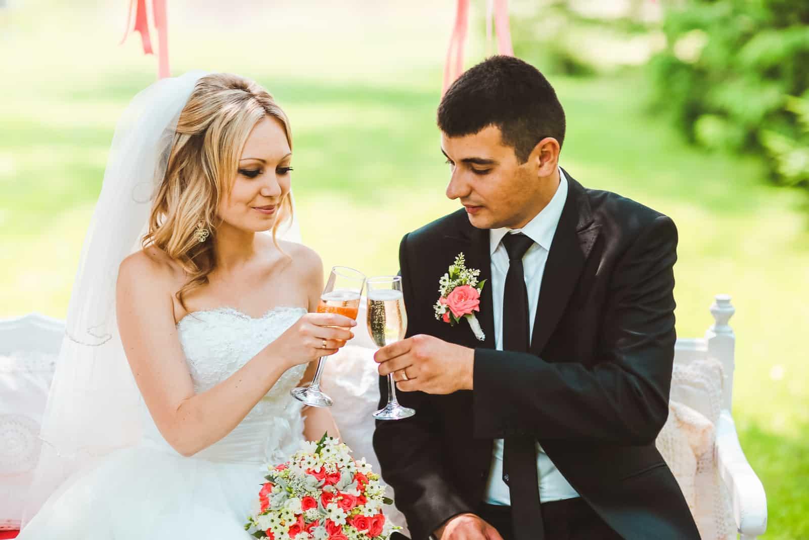 Das Brautpaar auf der Bank röstet mit Champagner