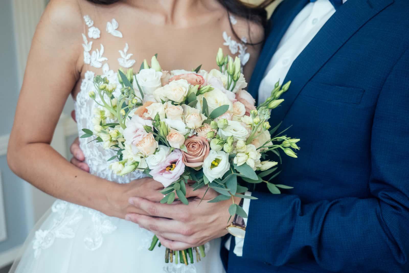 Das Brautpaar hält einen Blumenstrauß
