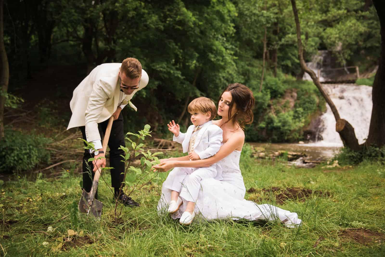 Das Brautpaar hat Spaß mit einem kleinen Jungen