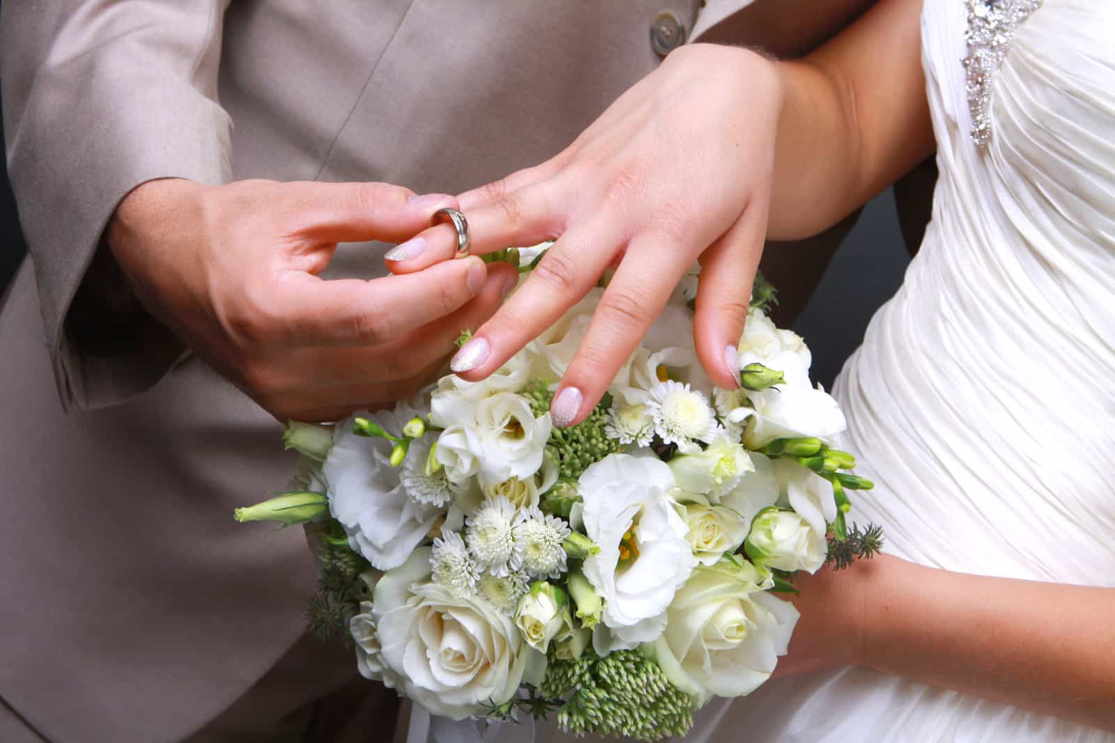 Der Bräutigam legt der Braut einen Ehering auf die Hand