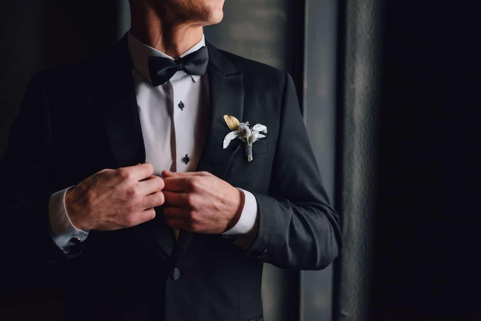 Der Bräutigam zieht eine Smokingjacke an