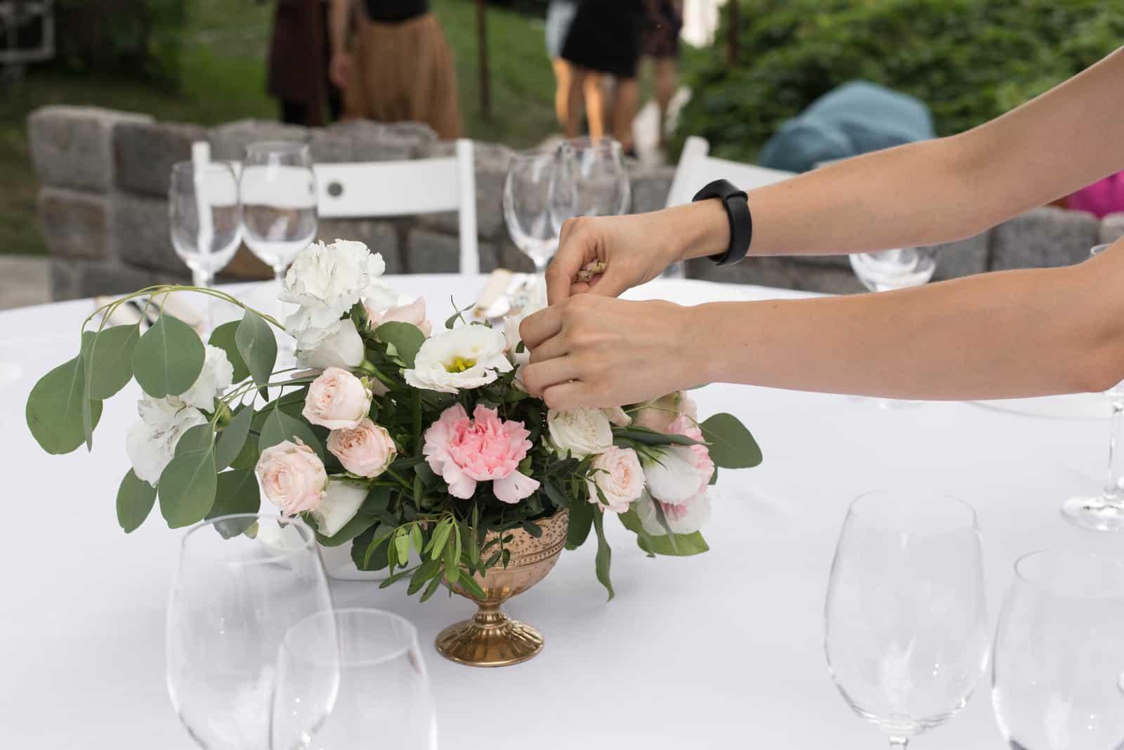 Der Kellner schmückt den Hochzeitstisch