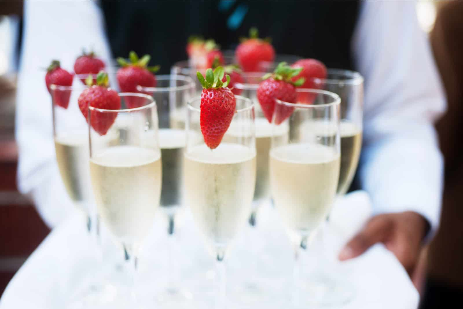 Der Kellner serviert Champagner mit Erdbeeren
