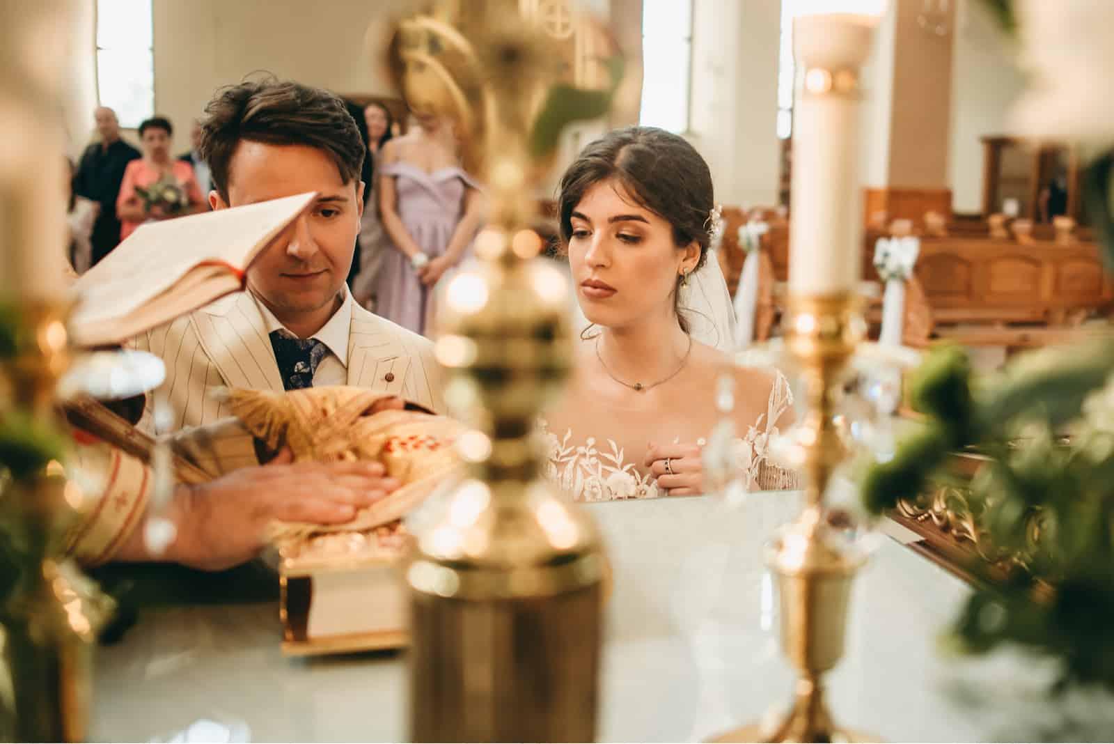Der Priester gibt den schönen Jungvermählten einen Segen