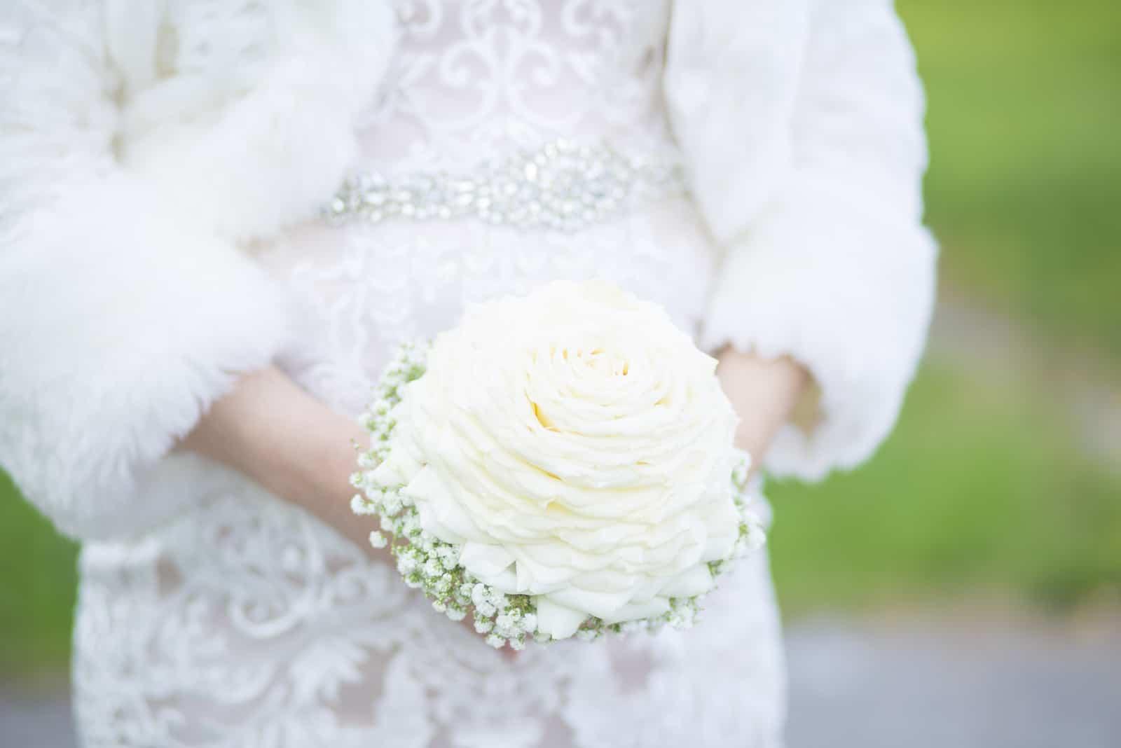 Die Braut hält einen Biedermeier-Strauß in den Händen