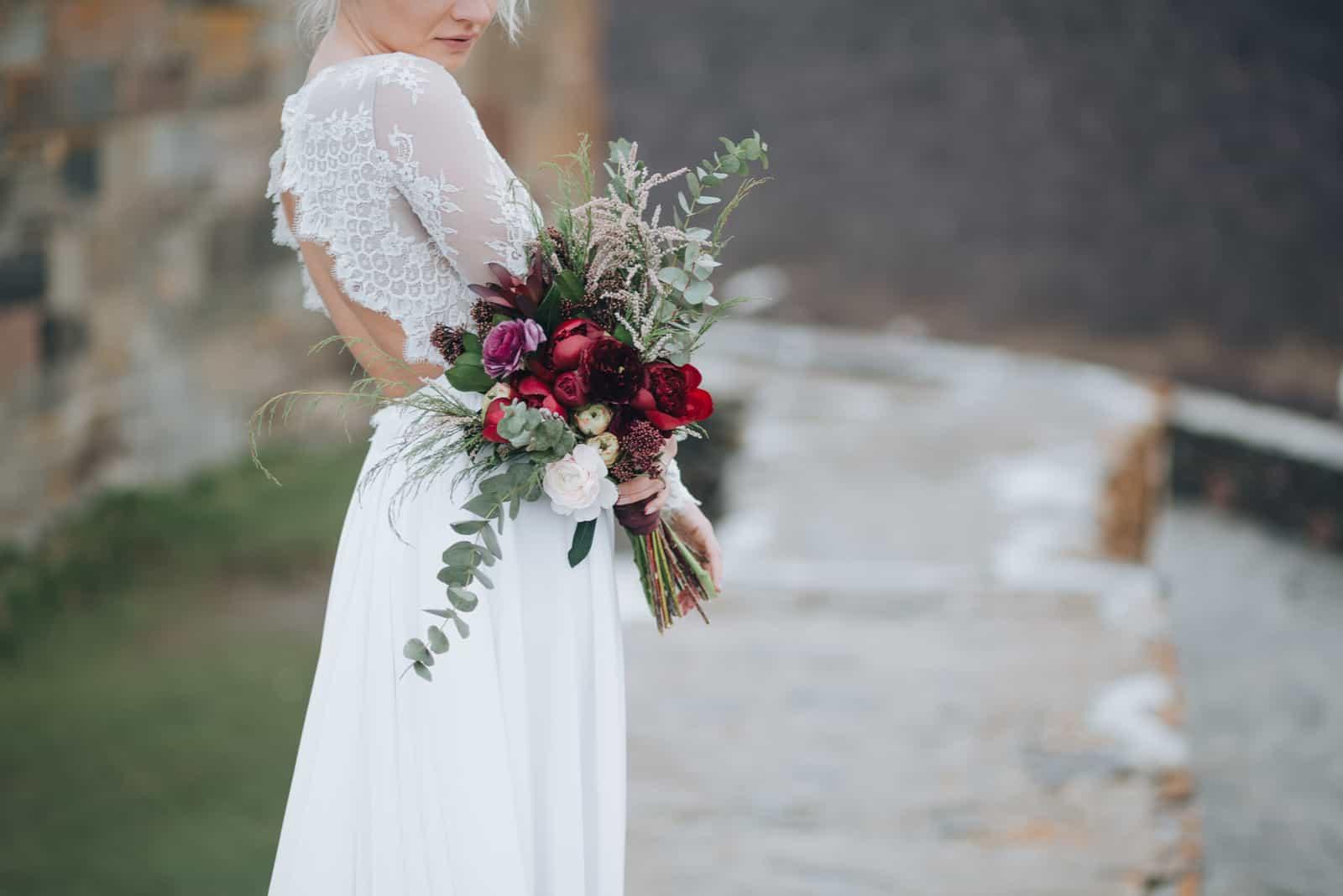 Die Braut mit einem Blumenstrauß in der Hand steht