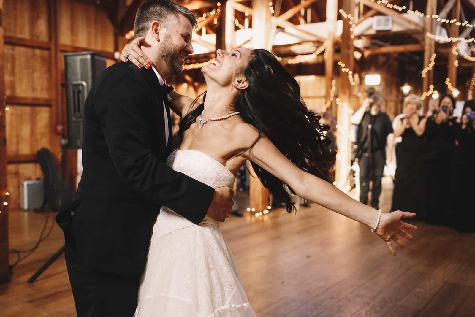 Die Braut schüttelt ihr dunkles Haar, während sie mit einem Bräutigam in einer Holzhalle tanzt
