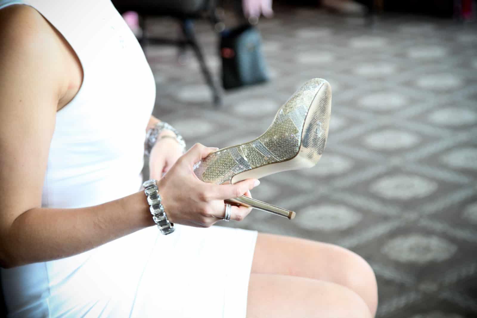 Die Braut sitzt auf einem Stuhl und bewacht ihre Sandale