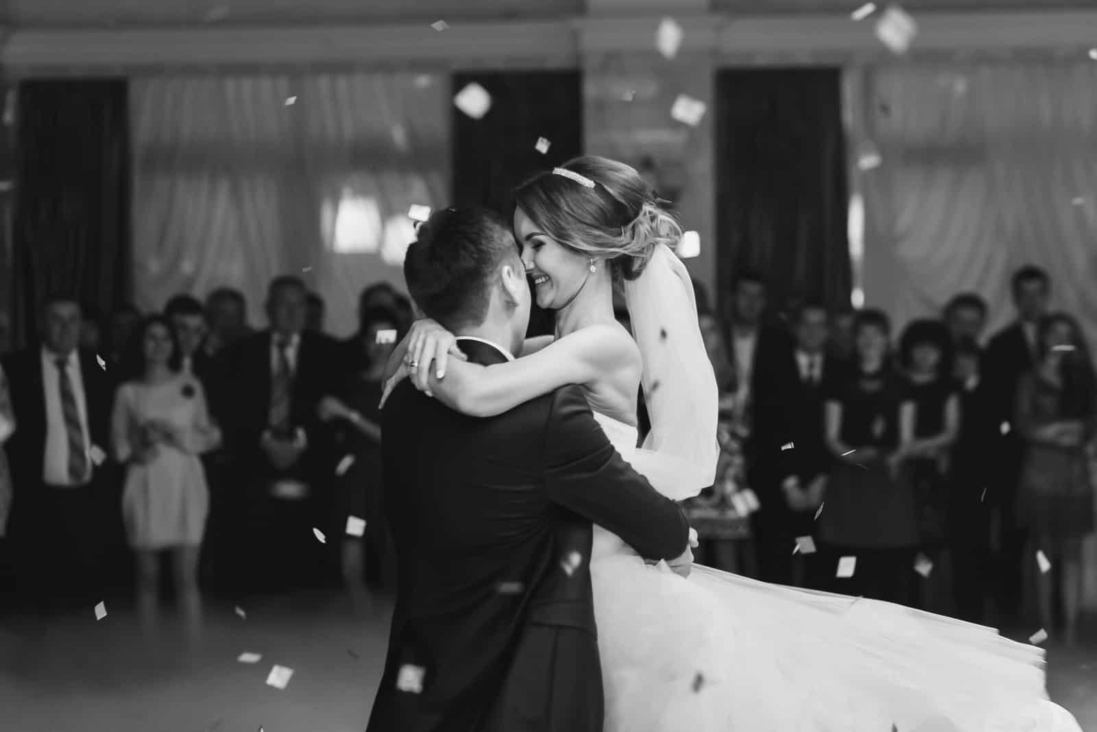Die Braut umarmt den Verlobten, während sie im Restaurant tanzt