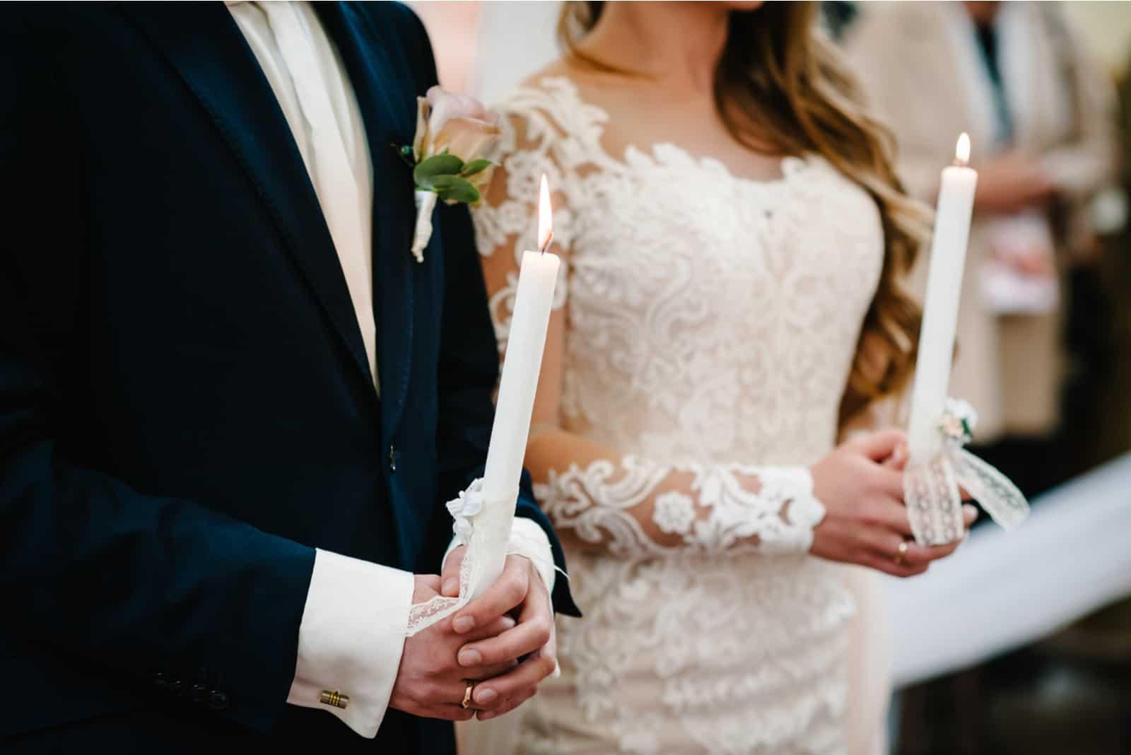 Die Jungvermählten auf der Hochzeit stehen mit Kerzen in den Händen