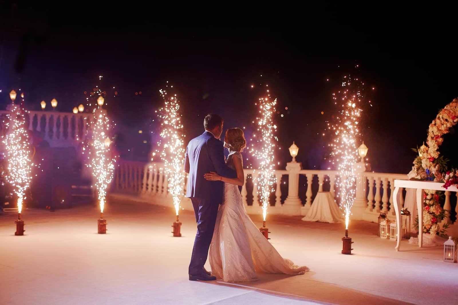 Die Jungvermählten tanzen den ersten Tanz auf der Terrasse mit Sprinklern